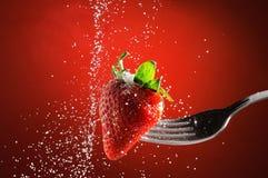 Erdbeere auf einer Gabel bohrte fallendes Zuckerdetail durch lizenzfreie stockfotografie