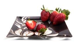 Erdbeere auf einer schwarzen glänzenden Platte Stockfotografie