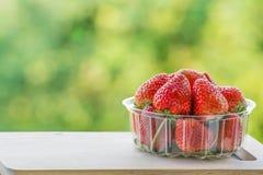 Erdbeere auf Holz- und Unschärfehintergrund Stockbild