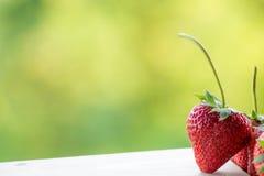 Erdbeere auf Holz- und Unschärfehintergrund Lizenzfreie Stockfotos