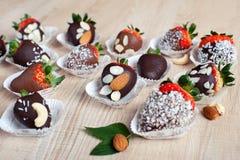 Erdbeere bedeckt mit Milch und dunklem Schokoladen- und Kokosnussflakfeuer Stockbilder