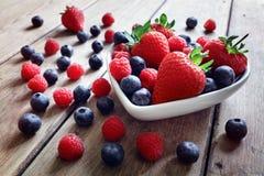 Erdbeere, Blaubeere und Himbeere tragen in einer Schüssel Früchte stockbild