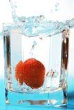Erdbeere, die in ein Glas mit Wasser fällt Lizenzfreie Stockfotos