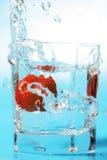 Erdbeere, die in ein Glas mit Wasser fällt Lizenzfreies Stockfoto