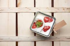 Erdbeere, die in einen Behälter Milch fällt Lizenzfreies Stockfoto