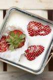 Erdbeere, die in Milch fällt und spritzt Lizenzfreies Stockfoto