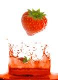 Erdbeere, die in Saft fällt. Lizenzfreies Stockbild
