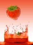 Erdbeere, die in Saft fällt Stockbilder