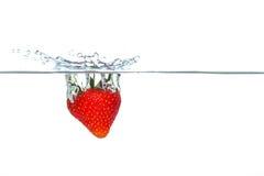 Erdbeere, die in Wasser mit einem Spritzen fällt Lizenzfreies Stockfoto