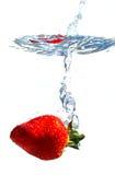 Erdbeere, die Wasser spritzt lizenzfreie stockbilder