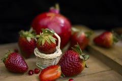 Erdbeere in einem kleinen Basketball auf hölzernem Brett mit Fruchtcremegranatapfel und anderen Erdbeeren in einem dunklen Hinter stockfoto