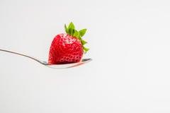 Erdbeere in einem Löffel mit einem weißen Hintergrund Stockfotografie