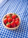 Erdbeere in einer hölzernen Schale auf blauer und weißer karierter Gewebebeschaffenheit stockbilder