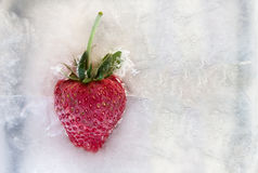 Erdbeere eingefroren im Eis stockfotografie
