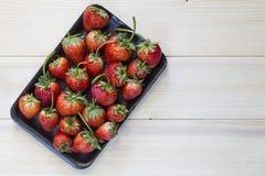 Erdbeere im Behälter auf hölzernem hinterem Boden Lizenzfreies Stockfoto