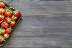 Erdbeere im Behälter auf hölzernem hinterem Boden lizenzfreie stockfotos