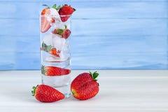 Erdbeere im Guss des Cocktails mit Eis auf blauem Hintergrund mit Erdbeere auf die Oberseite stockbilder