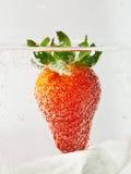 Erdbeere im Wasser mit Blasen als Symbol der romantischen SommerCocktailpartys auf dem Strand Stockbilder