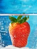 Erdbeere im Wasser mit Blasen auf einem abstrakten Hintergrund als Symbol der romantischen SommerCocktailpartys auf dem Strand Lizenzfreie Stockfotografie