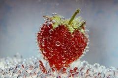 Erdbeere mit Blasen auf blauem Hintergrund Stockfotos