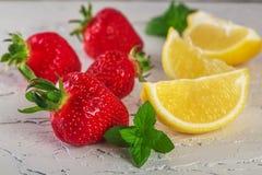 Erdbeere mit lemony Minze auf weißem Stein Stockbilder