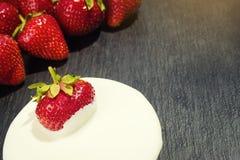 Erdbeere mit Sauerrahm in der Hand, Erdbeeren im Korb, Stroh Lizenzfreies Stockbild