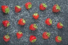 Erdbeere mit Zucker auf schwarzem Stein von der Spitze Stockbilder