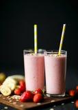 Erdbeere- und Banane Smoothie im Glas auf schwarzem Hintergrund Stockfoto