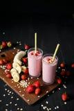 Erdbeere- und Banane Smoothie im Glas auf schwarzem Hintergrund Stockbild