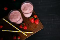 Erdbeere- und Banane Smoothie im Glas auf schwarzem Hintergrund Stockfotografie