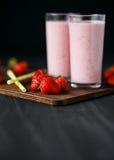 Erdbeere- und Banane Smoothie im Glas auf schwarzem Hintergrund Lizenzfreie Stockfotografie