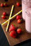 Erdbeere- und Banane Smoothie im Glas auf schwarzem Hintergrund Lizenzfreies Stockbild