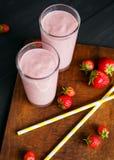 Erdbeere- und Banane Smoothie im Glas auf schwarzem Hintergrund Lizenzfreie Stockfotos