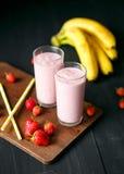 Erdbeere- und Banane Smoothie im Glas auf schwarzem Hintergrund Stockbilder