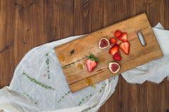 Erdbeere und Feigen auf einem hölzernen Brett Stockfotografie