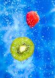 Erdbeere- und Kiwifrucht in einem Wasser spritzen Lizenzfreie Stockfotografie