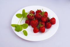 Erdbeere und Minze auf einer Platte Lizenzfreie Stockfotografie