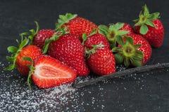 Erdbeere, Vanille und Zucker auf dem schwarzen Hintergrund Lizenzfreie Stockfotos
