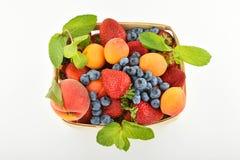 Erdbeeren, Aprikosen, Blaubeeren, Pfirsich im Korb an lokalisiert Stockfotos