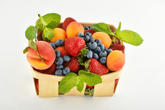 Erdbeeren, Aprikosen, Blaubeeren, Pfirsich im Korb an lokalisiert Stockfotografie