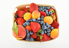Erdbeeren, Aprikosen, Blaubeeren, Pfirsich im Korb an lokalisiert Lizenzfreies Stockbild