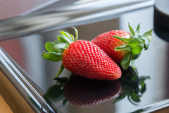 2 Erdbeeren auf einem schwarzen Hintergrund mit Reflexion Stockfoto