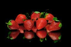 Erdbeeren auf einem schwarzen Hintergrund mit Spiegelreflexion Stockbilder