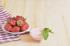 Erdbeeren auf einer Untertasse auf einem hellen Holztisch Stockfoto