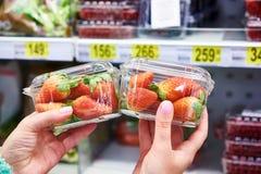Erdbeeren in den Händen des Käufers am Speicher Lizenzfreie Stockfotos