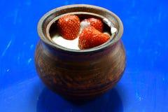 Erdbeeren in der Creme auf einem blauen Hintergrund Lizenzfreie Stockfotografie