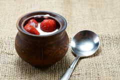 Erdbeeren in der Creme in den Lehmwaren auf Sackleinen Stockfotografie