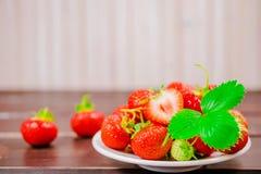 Erdbeeren in der Schüssel auf Holztisch mit zurückhaltendem und Kopie spacen Lizenzfreie Stockfotos