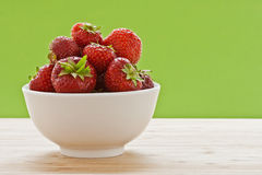 Erdbeeren in der Schüssel vor grünem Hintergrund II Stockbilder