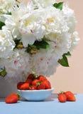 Erdbeeren in der Untertasse auf Hintergrund von weißen Pfingstrosen Lizenzfreie Stockfotografie